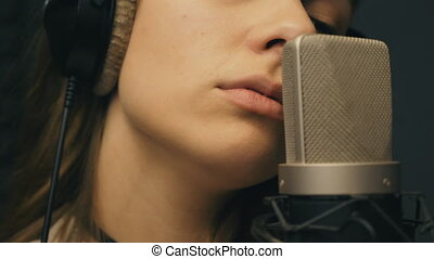 Beautiful girl singing in sound studio. Young singer emotionally recording new song. Lady sings to microphone. Working of creative musician. Show business concept. Slow motion Close up