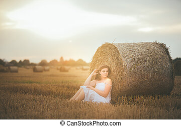 Beautiful Girl Sits in a Field with a Bales of Hay at Sunset