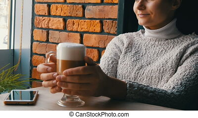 Beautiful girl sits in cozy cafe pensively smiling drinks...
