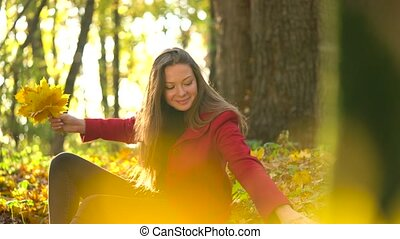 Beautiful girl sits in the autumn forest and collects a bouquet of yellow maple leaves