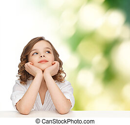 beautiful girl sitting at table and looking up