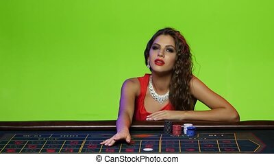 Beautiful girl sitting at the poker table in a casino -...