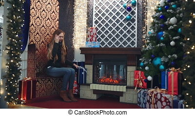 beautiful girl sitting by the fireplace a portrait of a young woman, the woman sitting in a chair near the Christmas tree
