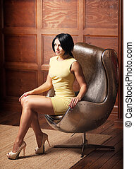 beautiful girl sitting in a leather chair