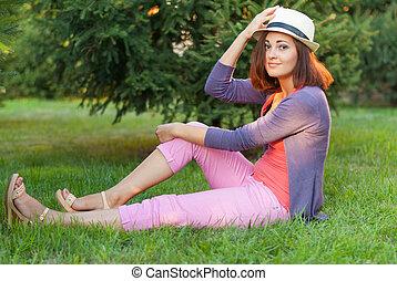 Beautiful girl sitting in the green grass.