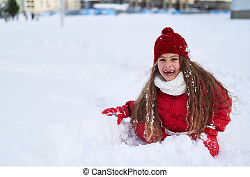beautiful girl sitting in the snow and laughing