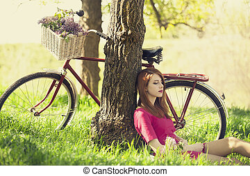 Beautiful girl sitting near bike and tree at rest in forest....