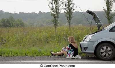 Beautiful girl sitting near her broken car on a country road and calling cellphone