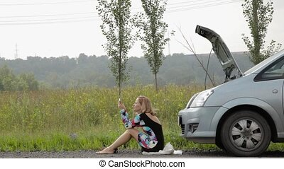 Beautiful girl sitting near her broken car on a country road...