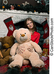 Beautiful girl sitting near the fireplace in an embrace with a fluffy beige teddy bear