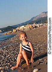 Beautiful girl sitting on a beach