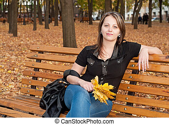 Beautiful girl sitting on a bench in autumn park