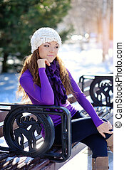 Beautiful girl sitting on a bench in winter