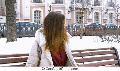 Beautiful girl sitting on a bench in winter, waiting for his friend, talking on the phone.