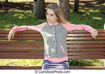 Beautiful girl sitting on a bench