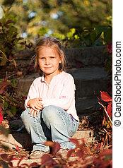 Beautiful girl sitting on a brick stairs