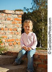 Beautiful girl sitting on a brick s