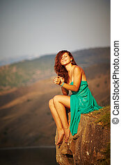Beautiful girl sitting on a cliff