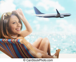 Beautiful girl sitting on a deck chair at the beach at sunset with airplane on background