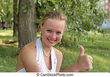 Beautiful girl sitting on a park with thumb up
