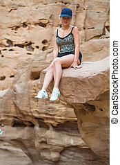 girl sitting on a rock