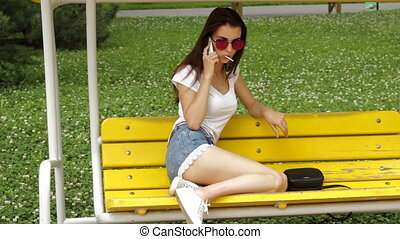 beautiful girl sitting on a seesaw licks a lollipop and talking on the phone