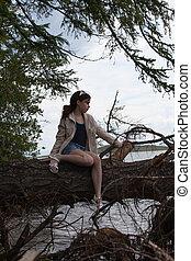 Beautiful girl sitting on a tree