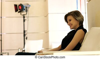 Beautiful girl sitting on couch in studio and laughs - Young...