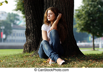 Beautiful girl sitting on grass