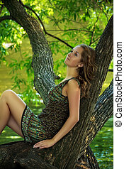 girl sitting on large tree