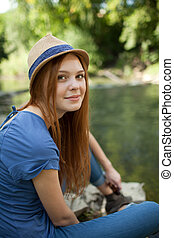 beautiful girl sitting on the bank of the river