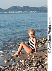 Beautiful girl sitting on the beach