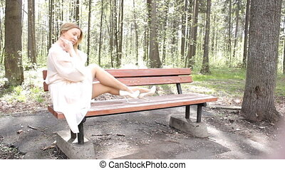 Beautiful girl sitting on the bench and smiling to the camera