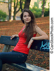 Beautiful girl sitting on the bench in the park and thinking