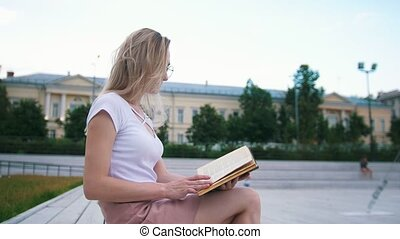 Beautiful girl sitting on the bench reading a book in the urban park