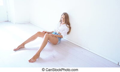 beautiful girl sitting on the floor in a white room