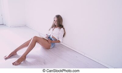 beautiful girl sitting on the floor in a white room reading a book