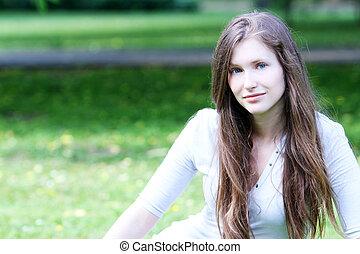 Beautiful girl sitting on the grass