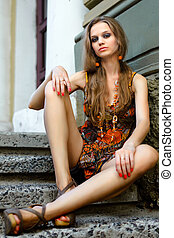 beautiful girl sitting on the street