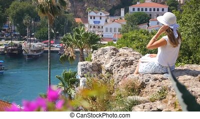 Beautiful girl sitting with a book on the rocks