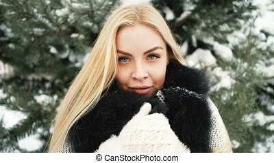 Beautiful girl smiles against background of snow covered forest.