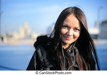 Beautiful girl smiling and  listening portable music outdoors in winter city. Shallow DOF, focus on eyes.