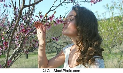 Beautiful girl sniffs the flowering tree outdoors