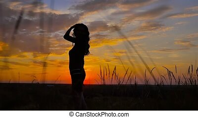 beautiful girl standing in a field at sunset slow motion video