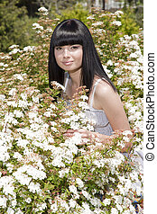 beautiful girl standing in a field with white flowers