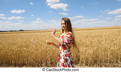 beautiful girl standing in a wheat field smiles and puts bubbles