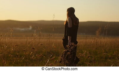 Beautiful girl standing in field at sunset.