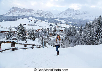 Beautiful girl standing in the mountains during winter with an astonishing view of the mountain village.