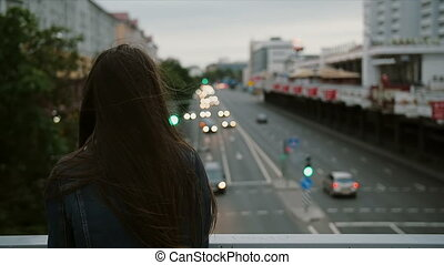 beautiful girl standing on bridge, looks at city, then turns to the camera and smiling. Wind blows her hair. slow motion