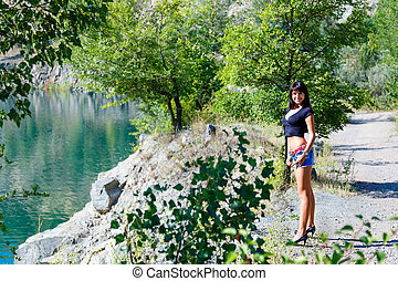 beautiful girl standing on the shore of a mountain river